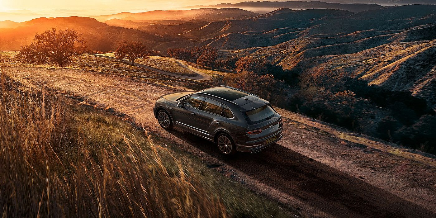 new-bentley-bentayga-v8-driving-on-dirt-road-at-sunset-in-hallmark-paint-2020